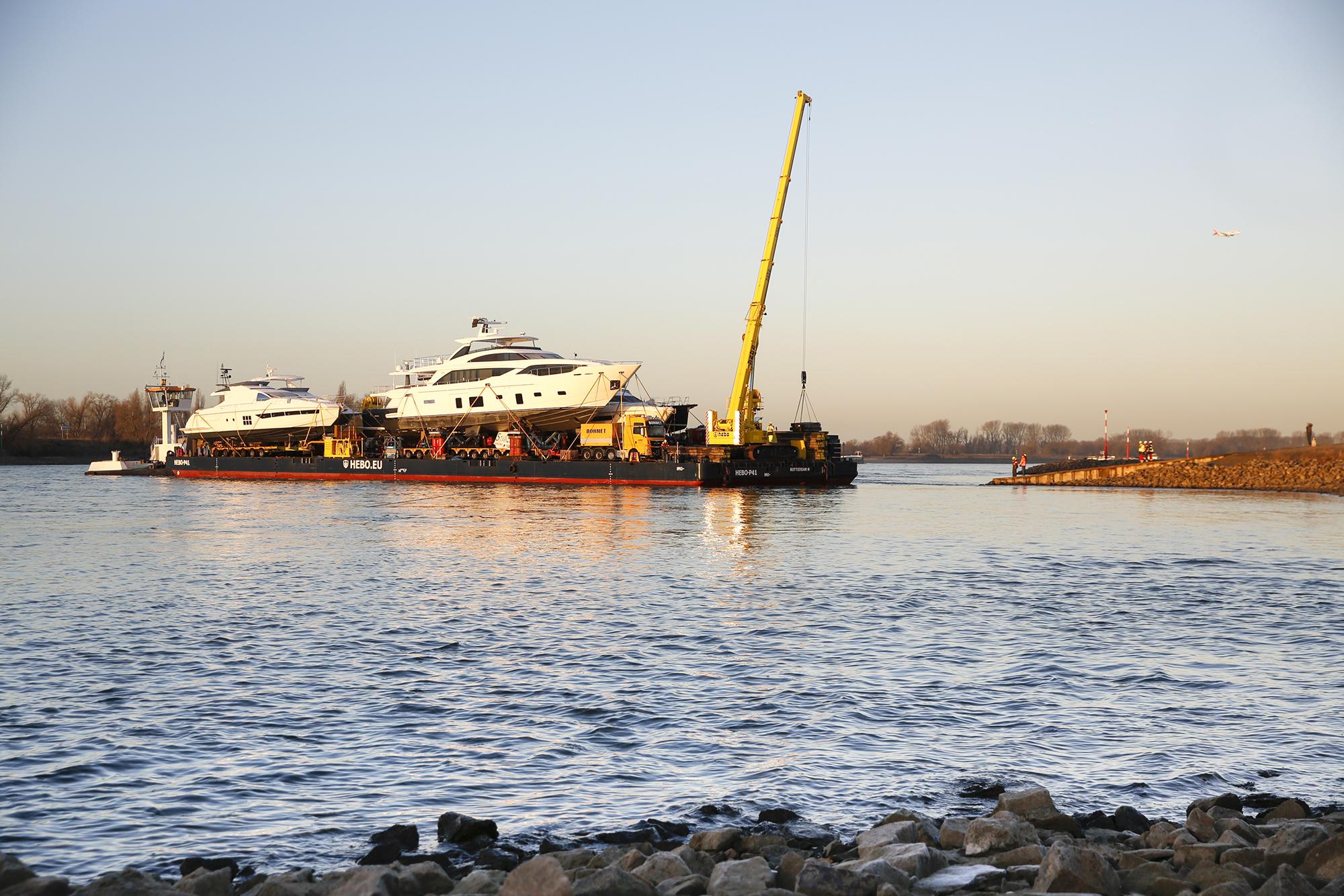 Das neue Jahr beginnt in Düsseldorf mit einem spektakulären Schiffstransport: auf einem 110 Meter langen Ponton reisen sieben Luxus-Motor- und -Segelyachten zur boot 2017. Die Schwergewichte haben vom 21. bis 29. Januar ihre temporäre Heimat in der Halle 6 und der Halle 16 und präsentieren sich dort den staunenden Besuchern. Star des Transports ist die Princess 30M (99 Fuß). Die stolze Prinzessin – auf der boot in der Halle 6/Stand B21 zu bestaunen - aus dem Vereinigten Königreich ist gleichzeitig auch die größte und mit einem Einstiegspreis von 7,4 Millionen Euro auch die teuerste Yacht, die es auf der boot zu sehen gibt. Nicht minder schön und schnittig sind die Italienerinnen aus den Azimut (Halle 6/Stand D57/D58) und Ferretti (Halle 6/Stand D27/E21) Werften. Die Azimut Magellano M66 (20,15 Meter) kostet 1,85 Millionen Euro, die Azimut 72 (22,64 Meter) wechselt für 2,75 Millionen Euro den Besitzer, die Azimut 77 S (23,6 Meter) gibt es für 3,3 Millionen Euro und der Preis für die Ferretti 700 Yachts (21,58 Meter) liegt bei 2,43 Millionen Euro. Hinzu kommt mit der Monte Carlo 70 (21,3 Meter) für über 3 Millionen Euro ein französisch/italienisches Schmuckstück (Halle 6/Stand B27). Ebenfalls an Bord ist die britische Oyster 675 (21,07 Meter). Das klassisch-schöne Segelschiff (Halle 16/Stand C58) kostet 2,48 Millionen britische Pfund (umgerechnet ca. 2,92 Millionen Euro). Die Schiffe traten ihre Reise über den Rhein am 2. Januar im niederländischen Rotterdam an. Für die nötige Antriebskraft sorgte Schubschiff Catherina 4, dass das Ponton mit einer maximalen Schubkraft von 4,7 Knoten (8,7 kmh) in etwas mehr als drei Tagen zum Düsseldorfer Messeanleger transportierte. Am frühen Donnerstagmorgen erreichte es mit seiner wertvollen Fracht sein Ziel. Dort waren die erfahrenen Transporteure des Logistikunternehmens Kühne und Nagel schnell zur Stelle und bauten eine Transportbrücke von der Düsseldorfer Messerampe zum Ponton.  Über eine Seilwinde w