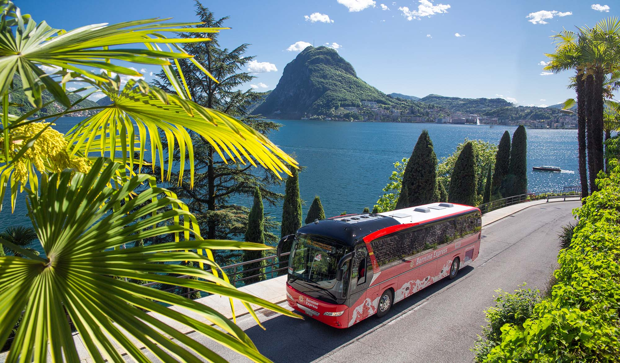 Bernina Express - Der Bernina Express Bus verbindet Tirano mit Lugano. Hier am Lago di Lugano. Bernina Express - The Bernina Express Bus provides a link between Tirano and Lugano. Shown here by Lake Lugano. Bernina Express - L'autobus collega Tirano a Lugano. Qui presso il Lago di Lugano. Copyright by Rhaetische Bahn By-line: swiss-image.ch/Christof Sonderegger