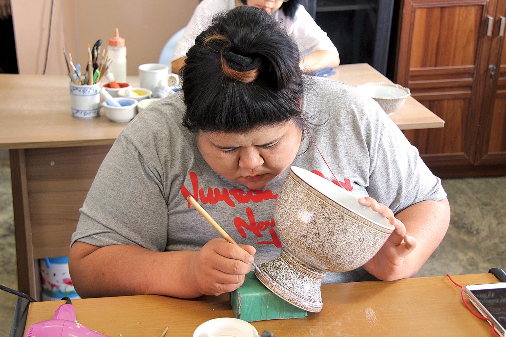 Майстриня розписую порцеляну в стилі бенджаронг
